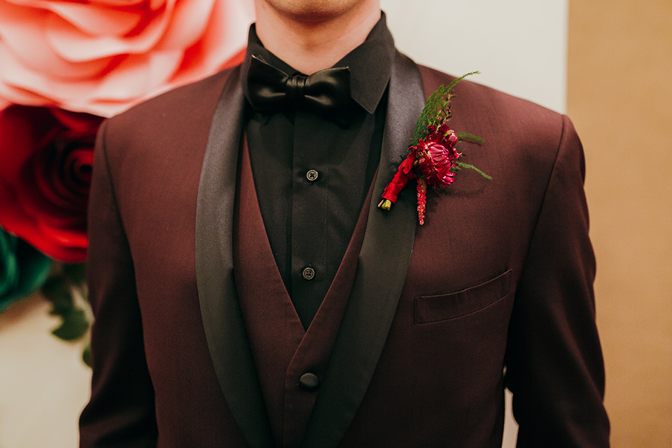 dia-de-los-muertos-shoot-close-up-on-groo-attire-burgundy-tuxedo-with-black-trim-a-black-shirt-and-a-faux-black-bow-tie
