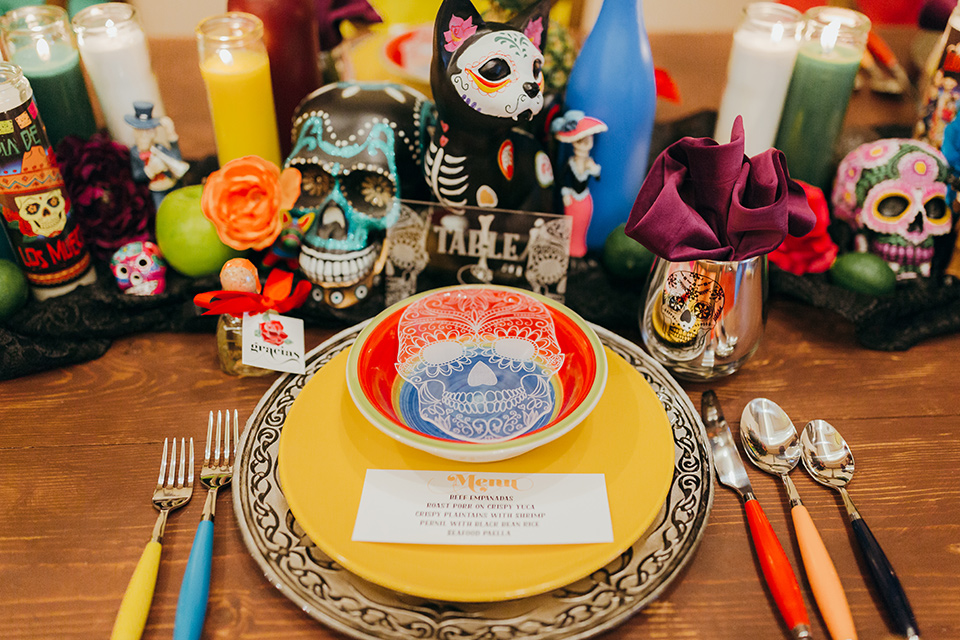 dia-de-los-muertos-shoot-table-decor-close-up-on-candles-yellow-plates-with-sugar-skull-details-color-décor-and-silverware