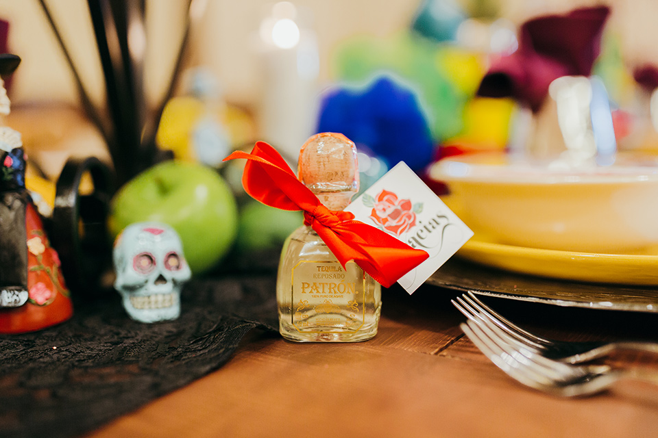 dia-de-los-muertos-shoot-table-decore-close-up-on-little-bottles-table-decor-close-up-on-candles-yellow-plates-with-sugar-skull-details-color-décor-and-silverware