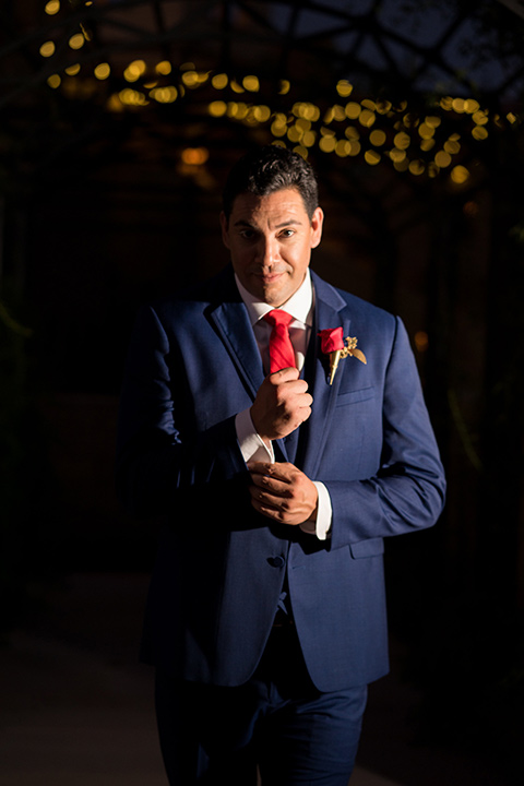 wonder-woman-meets-superman-groom-fixing-sleeve-groom-in-a-navy-suit-and-red-long-tie-with-red-rose-florals