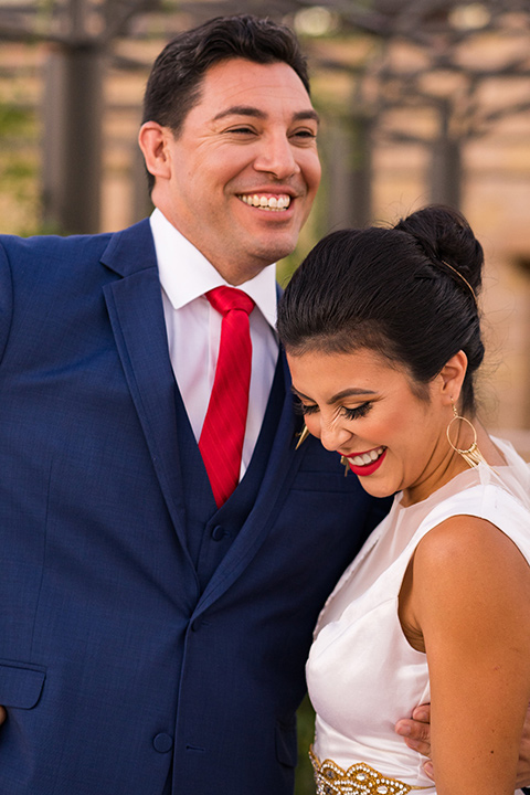 wonder-woman-meets-superman-laughing-bride-in-a-white-silk-dress-with-her-wonder-woman-head-piece-holding-onto-groom-in-a-navy-suit-and-red-long-tie-with-red-rose-florals