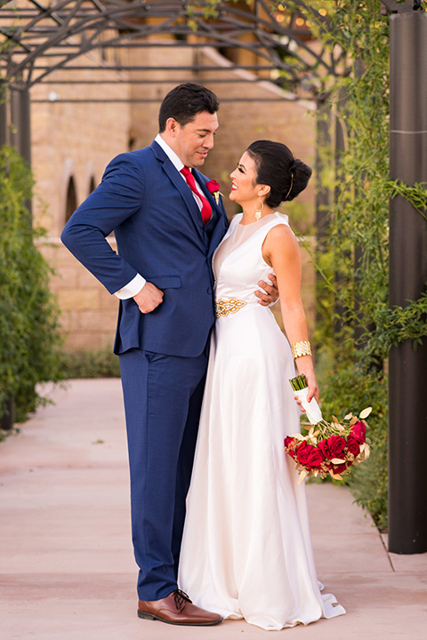wonder-woman-meets-superman-looking-at-each-other-bride-in-a-white-silk-dress-with-her-wonder-woman-head-piece-holding-onto-groom-in-a-navy-suit-and-red-long-tie-with-red-rose-florals