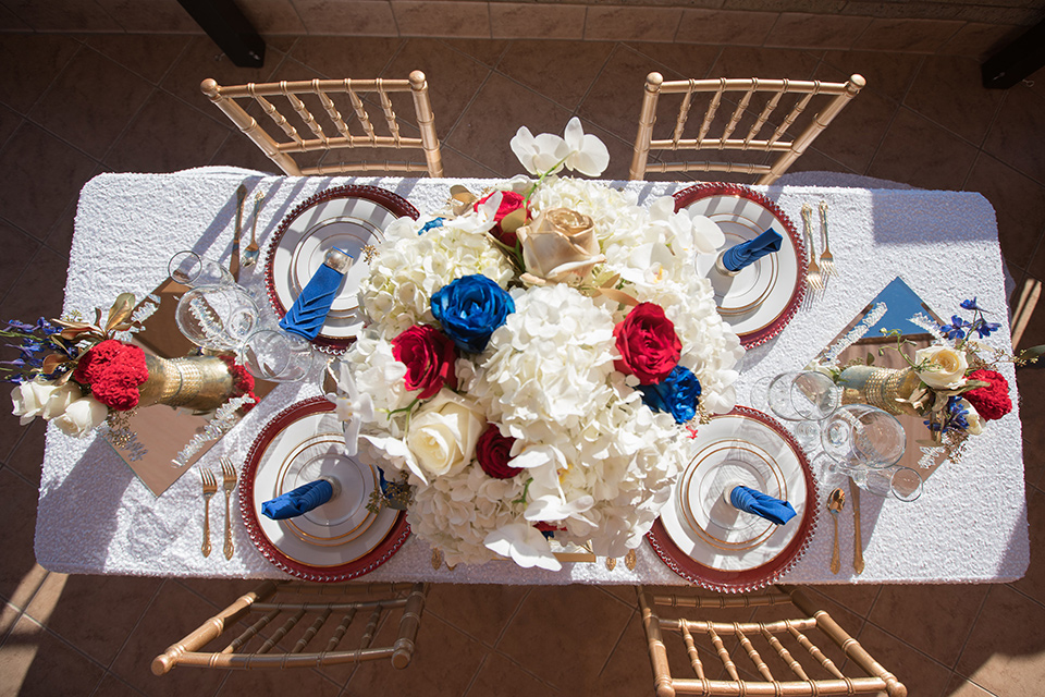 wonder-woman-meets-superman-placesetting-white-table-cloths-with-gold-chairs-and-accents-with-red-white-and-blue-florals-and-white-plates