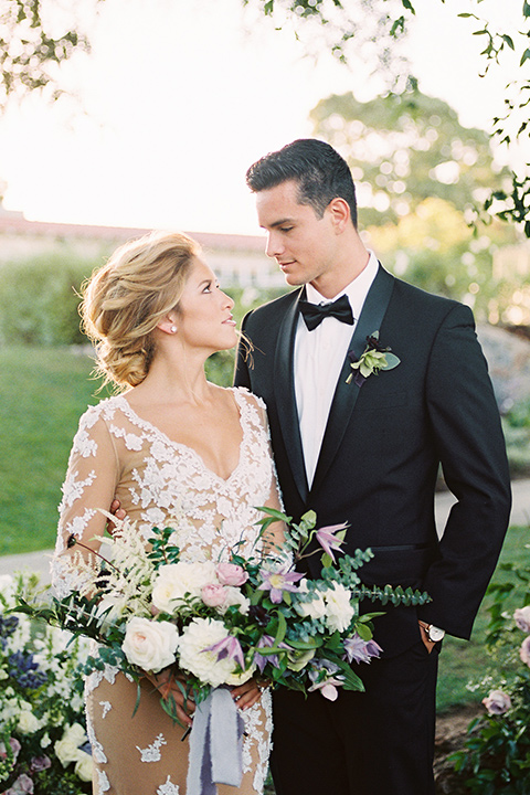 Inn-at-rancho-santa-fe-shoot-bride-and-groom-looking-at-each-other-holding-flowers-by-the-tree-close-up-bride-in-a-lace-gown-with-an-illusion-detailing-with-a-nude-underlay-with-her-hair-in-back-in-a-loose-bun-groom-in-a-black-tuxedo-with-black-blow-tie-and-a-white-and-black-olka-dot-pocket-square