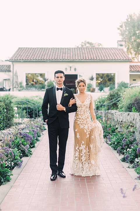 Inn-at-rancho-santa-fe-shoot-bride-and-groom-standing-in-garden-walk-way-holding-hands-bride-in-a-lace-gown-with-an-illusion-detailing-with-a-nude-underlay-with-her-hair-in-back-in-a-loose-bun-groom-in-a-black-tuxedo-with-black-blow-tie-and-a-white-and-black-polka-dot-pocket-square