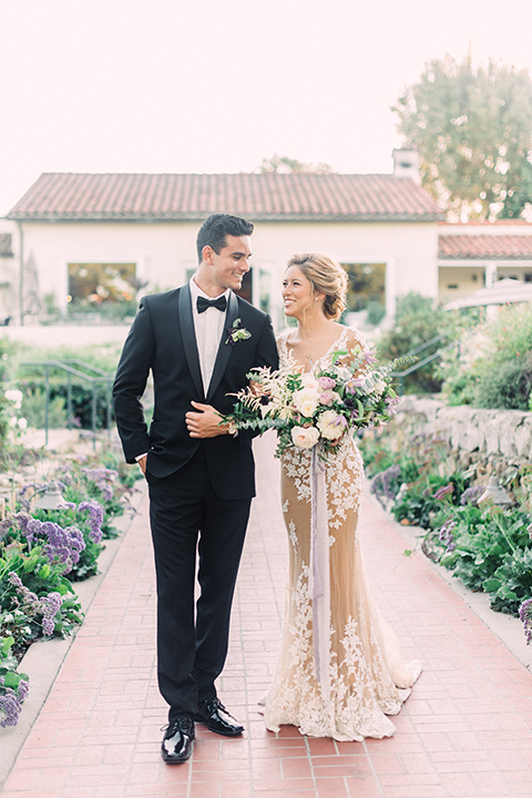 Inn-at-rancho-santa-fe-shoot-bride-and-groom-walking-bride-in-a-lace-gown-with-an-illusion-detailing-with-a-nude-underlay-with-her-hair-in-back-in-a-loose-bun-groom-in-a-black-tuxedo-with-black-blow-tie-and-a-white-and-black-olka-dot-pocket-square