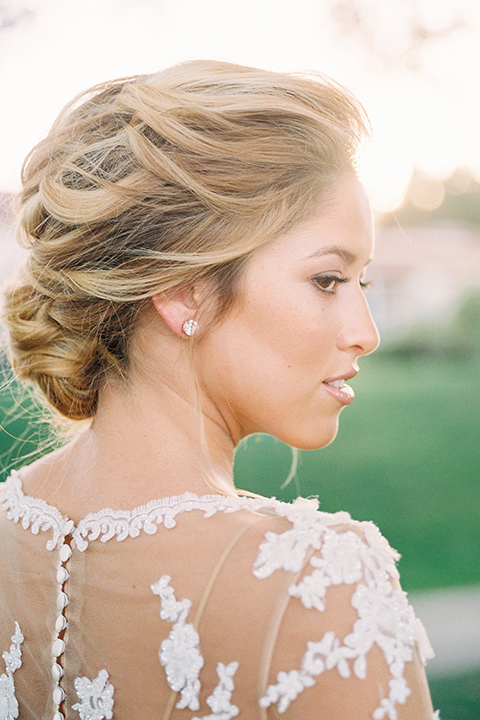 Inn-at-rancho-santa-fe-shoot-bride-close-up-focus-on-hair-bride-in-a-lace-gown-with-an-illusion-detailing-with-a-nude-underlay-with-her-hair-in-back-in-a-loose-bun