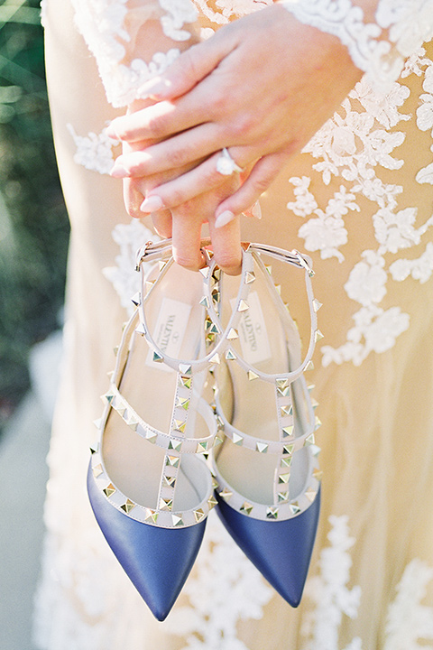 Inn-at-rancho-santa-fe-shoot-close-up-on-heels-bride-in-a-lace-gown-with-an-illusion-detailing-with-a-nude-underlay-with-cobalt-blue-heels-with-studs