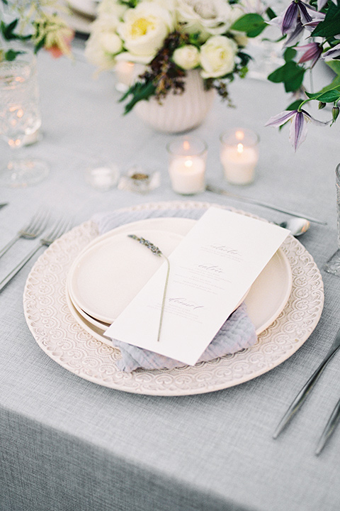 Inn-at-rancho-santa-fe-shoot-close-up-on-table-décor-white-plates-with-silver-chargers-with-mitallic-silverware-with-flowers-all-around