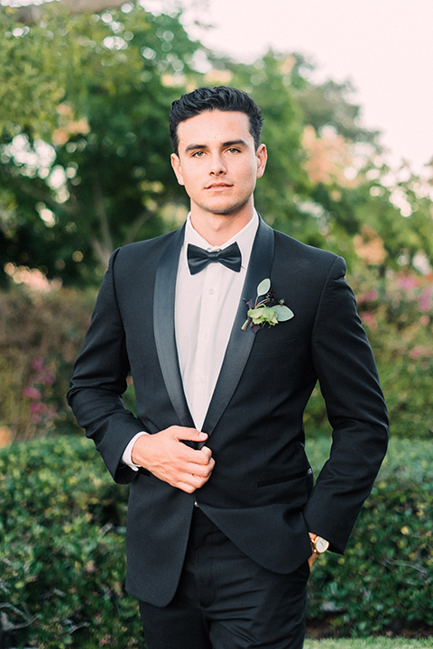 Inn-at-rancho-santa-fe-shoot-groom-along-standing-looking-straight-on-camera-groom-in-a-black-tuxedo-with-black-blow-tie-and-a-white-and-black-polka-dot-pocket-square