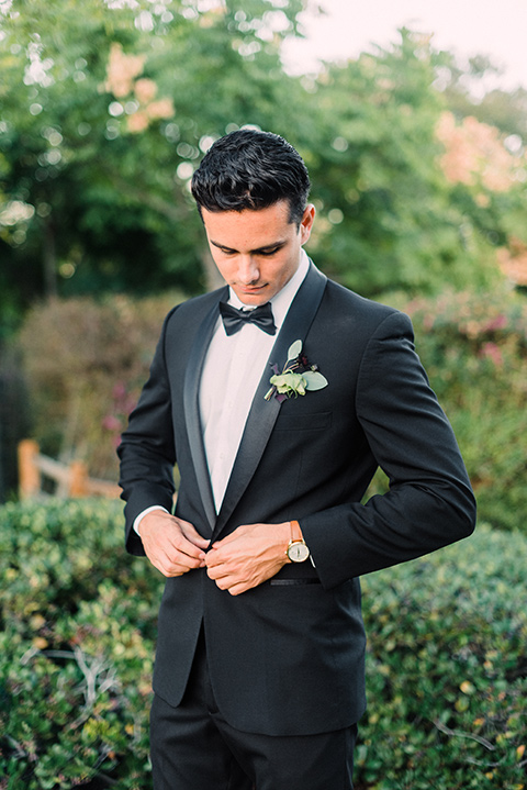 Inn-at-rancho-santa-fe-shoot-groom-buttoning-jacket-groom-along-standing-looking-straight-on-camera-groom-in-a-black-tuxedo-with-black-blow-tie-and-a-white-and-black-polka-dot-pocket-square