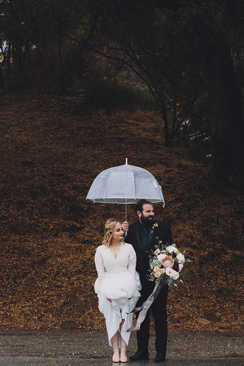 amanda-and-codys-wedding-at-the-1909-bride-and-groom-crossing-street-with-umbrella-bride-in-an-a-line-dress-with-a-tulle-skirt-and-lace-long-sleeve-bodice-groom-in-all-black-shawl-lapel-tuxedo