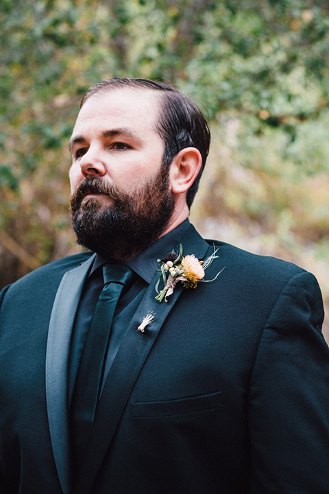 amanda-and-codys-wedding-at-the-1909-groom-in-all-black-shawl-lapel-tuxedo-and-a-small-hand-pin-on-the-lapel