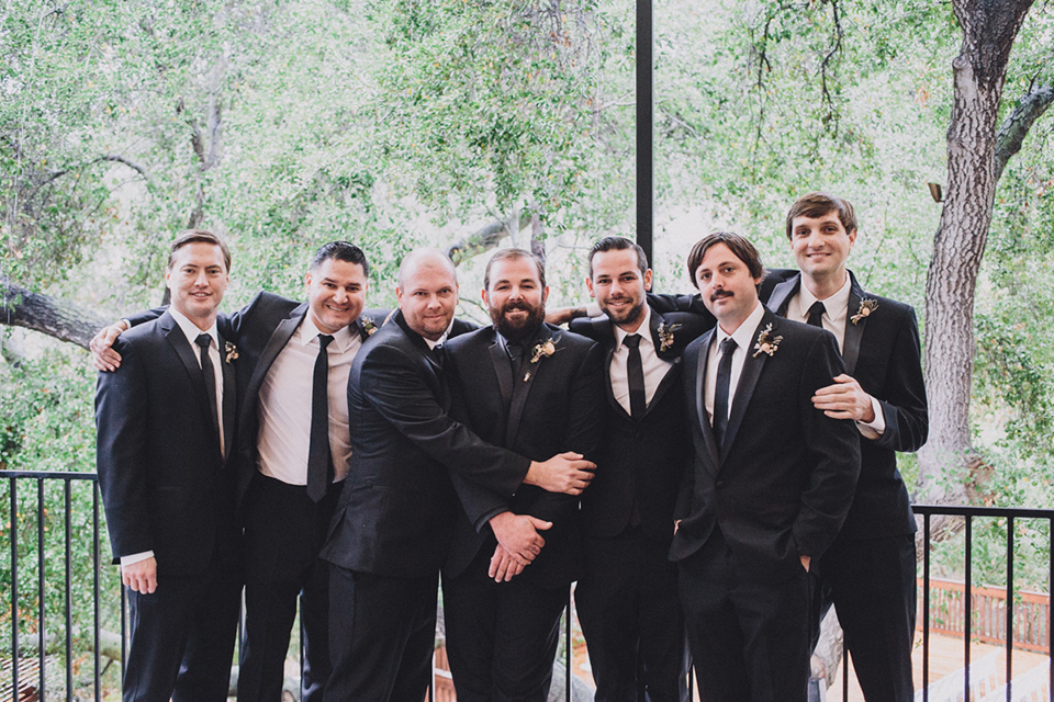 amanda-and-codys-wedding-at-the-1909-groomsmen-groom-in-all-black-shawl-lapel-tuxedo-with-black-shirt-groomsmen-in-same-tuxedo-with-a-white-shirt