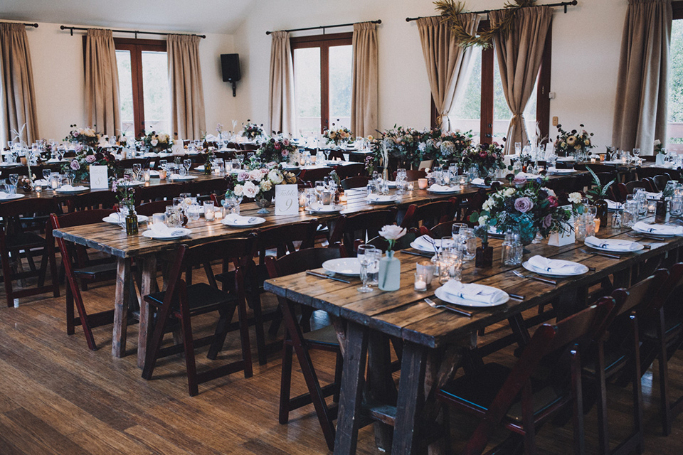 amanda-and-codys-wedding-at-the-1909-reception-set-up-rustic-deep-brown-wooden-tables-with-minimal-florals-and-simple-decor