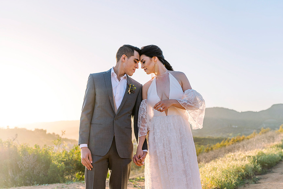 Emerald-peak-shoot-bride-and-groom-heads-touching-bride-in-a-bohemian-style-lace-dress-off-the-shoulder-groom-in-a-charcoal-grey-suit-with-a-tan-vest