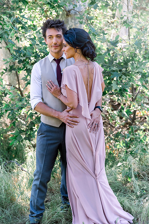 Emerald-peak-shoot-groomsman-and-bridesmaid-embracing-groomsman-in-charcoal-pants-tan-vests-and-a-burgundy-tie-bridesmaid-in-a-blush-flowing-dress