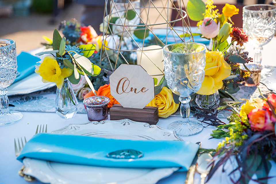 Emerald-peak-shoot-table-decor-gold-accented-candles-teal-napkins-and-charger-plates