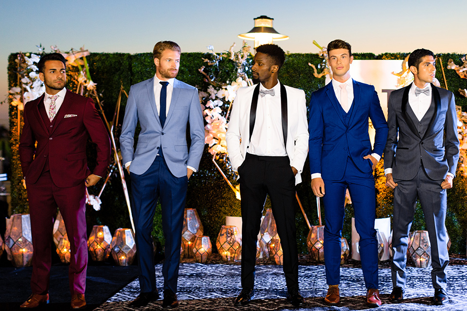 evolution-of-style-party-burgundy-model-on-the-end-guys-showing-off-latest-styles-starting-from-the-left-model-in-burgundy-suit-with-white-and-burgundy-floral-tie-next-model-in-dark-blue-ants-with-a-light-blue-suit-jacket-and-navy-tie-next-model-in-a-white-juxedo-jacket-with-black-trim-and-black-pants-next-model-in-cobalt-suit-with-blush-tie-and-brown-shoes-and-last-model-in-grey-tuxedo-with-black-trim at-the-fifth-restaurant
