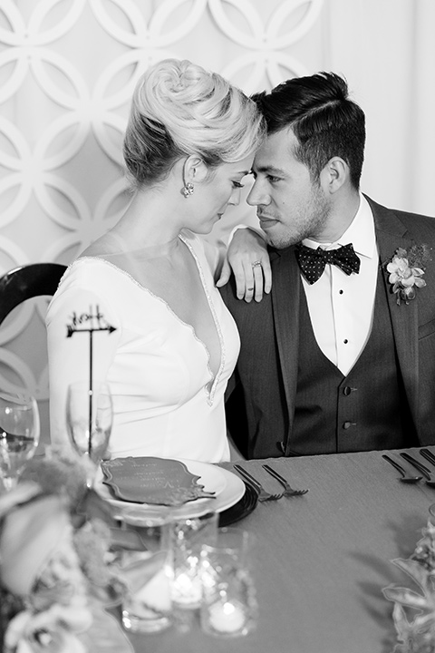 Exquisite-weddings-magazine-black-and-white-photo-of-bride-and-good-looking-at-each-other-bride-in-a-white-long-sleeved-dress-with-a-plunging-neckline-and-hair-in-a-bun-groom-in-a-grey-michael-kors-tuxedo-with-a-black-bowtie
