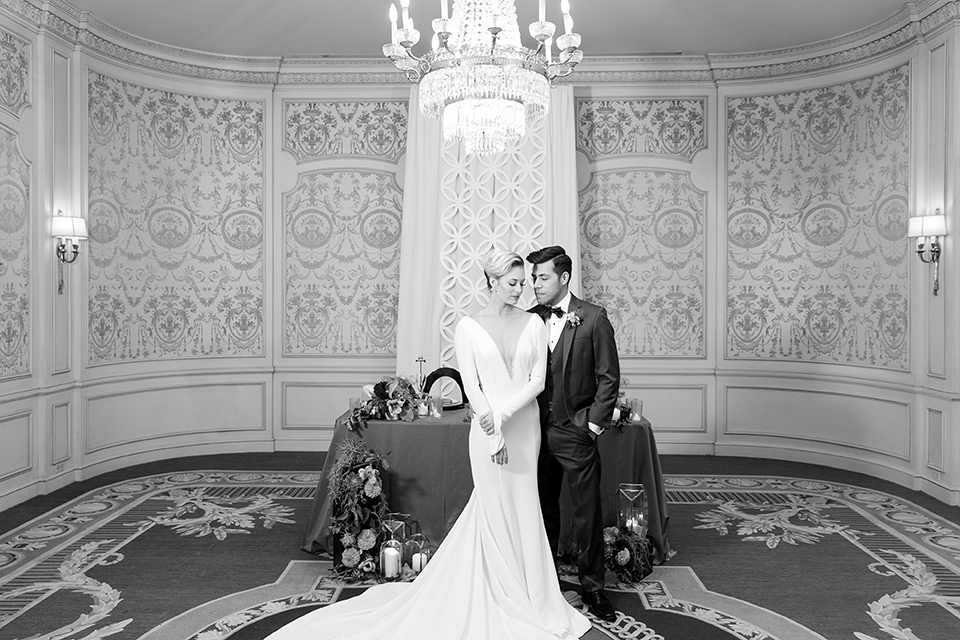 Exquisite-weddings-magazine-black-and-white-photo-of-bride-and-groom-at-sweetheart-table-bride-in-a-white-long-sleeved-dress-with-a-plunging-neckline-and-hair-in-a-bun-groom-in-a-grey-michael-kors-tuxedo-with-a-black-bowtie