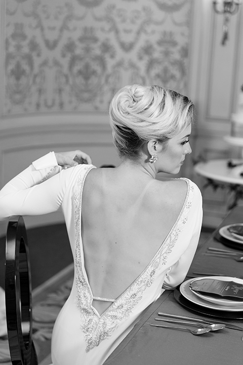 Exquisite-weddings-magazine-black-and-white-photo-of-detailing-on-bridal-gown-bride-in-a-white-long-sleeved-dress-with-a-plunging-neckline-and-hair-in-a-bun