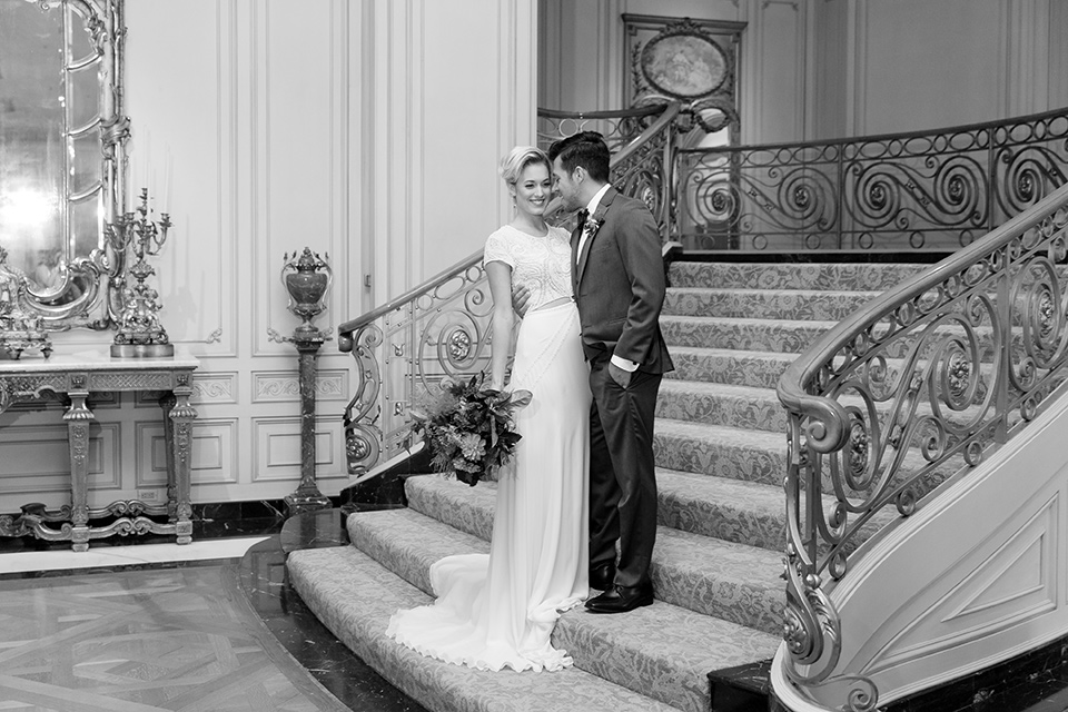Exquisite-weddings-magazine-black-and-white-photo-on-staircase-bride-in-a-white-long-sleeved-dress-with-a-plunging-neckline-and-hair-in-a-bun-groom-in-a-grey-michael-kors-tuxedo-with-a-black-bowtie