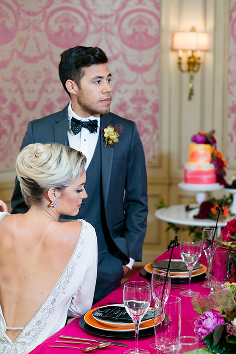 Exquisite-weddings-magazine-bride-and-groom-at-the-desserts-table-looking-away-bride-in-a-white-long-sleeved-dress-with-a-plunging-neckline-and-hair-in-a-bun-groom-in-a-grey-michael-kors-tuxedo-with-a-black-bowtie