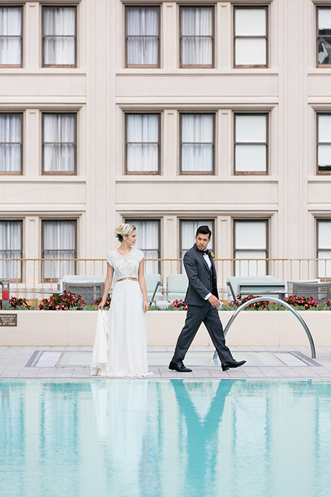 Exquisite-weddings-magazine-bride-and-groom-by-the-pool-bride-in-a-white-long-sleeved-dress-with-a-plunging-neckline-and-hair-in-a-bun-groom-in-a-grey-michael-kors-tuxedo-with-a-black-bowtie