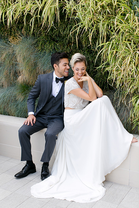 Exquisite-weddings-magazine-bride-and-groom-sitting-outside-laughing-bride-in-a-white-long-sleeved-dress-with-a-plunging-neckline-and-hair-in-a-bun-groom-in-a-grey-michael-kors-tuxedo-with-a-black-bowtie