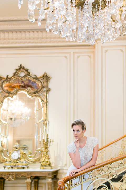 Exquisite-weddings-magazine-bride-leaning-on-staircase-bride-in-a-white-long-sleeved-dress-with-a-plunging-neckline-and-hair-in-a-bun