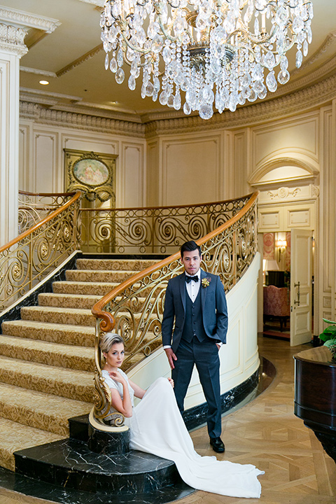 Exquisite-weddings-magazine-bride-sitting-on-stairs-groom-standing-next-to-her-bride-in-a-white-long-sleeved-dress-with-a-plunging-neckline-and-hair-in-a-bun-groom-in-a-grey-michael-kors-tuxedo-with-a-black-bowtie