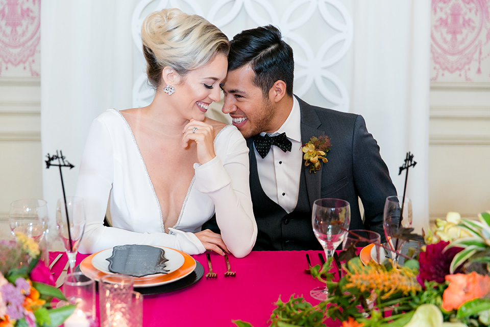 Exquisite-weddings-magazine-brode-and-groom-laughing-at-sweetheart-table-bride-in-a-white-long-sleeved-dress-with-a-plunging-neckline-and-hair-in-a-bun-groom-in-a-grey-michael-kors-tuxedo-with-a-black-bowtie