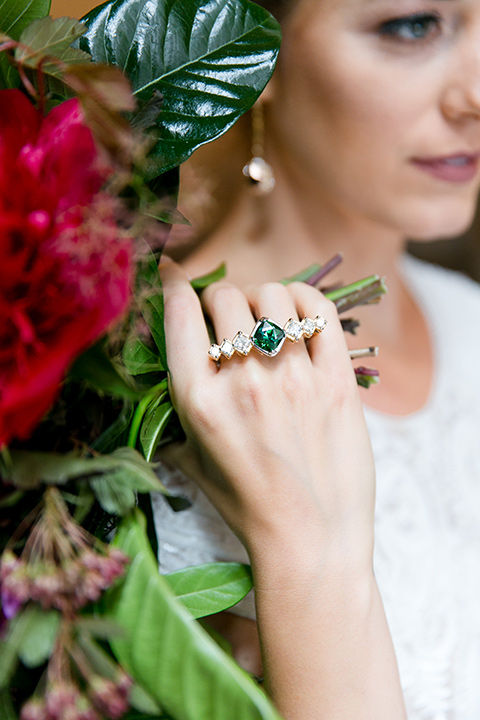 Exquisite-weddings-magazine-close-up-on-emerald-ring-bride-in-a-white-long-sleeved-dress-with-a-plunging-neckline-and-hair-in-a-bun-with-an-emerald-ring-and-a-bright-floral-arrangement