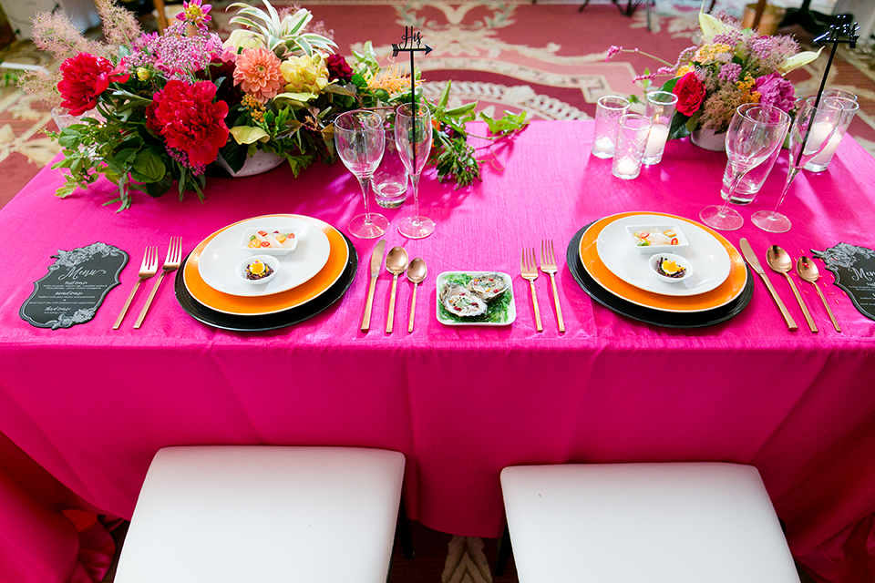Exquisite-weddings-magazine-close-up-on-table-hot-pink-linen-with-white-plates-and-gold-cutlery-with-bright-orange-and-green-floral-arrangements