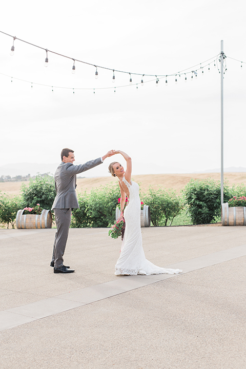 Temecula outdoor wedding at callaway winery bride form fitting lace gown with crystal beading and lace detail with open back design and beaded straps with groom grey notch lapel suit with matching vest and white dress shirt with long black skinny tie and pink floral boutonniere dancing