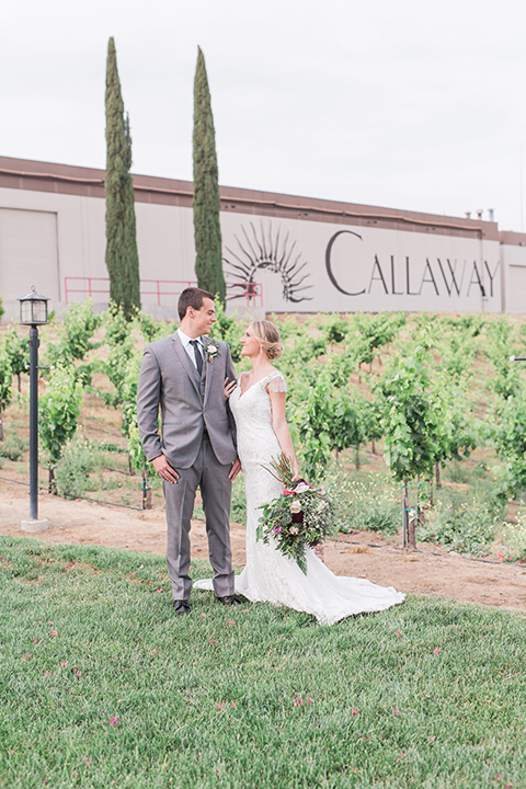 Temecula outdoor wedding at callaway winery bride form fitting lace gown with crystal beading and lace detail with open back design and beaded straps with groom grey notch lapel suit with matching vest and white dress shirt with long black skinny tie and pink floral boutonniere holding hands and bride holding pink and green floral bridal bouquet