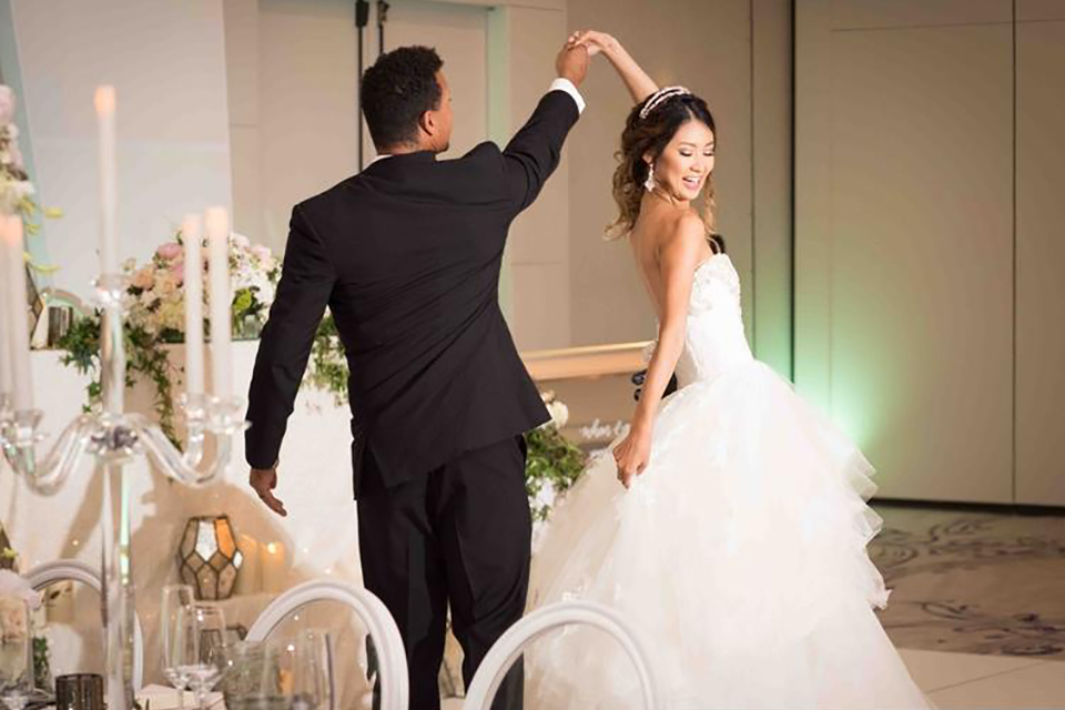 Classic glamour wedding shoot at the avenue of the arts hotel bride strapless ball gown with beaded detail on top with sweetheart neckline and groom black tuxedo with white dress shirt and long silver tie with matching vest and pocket square dancing