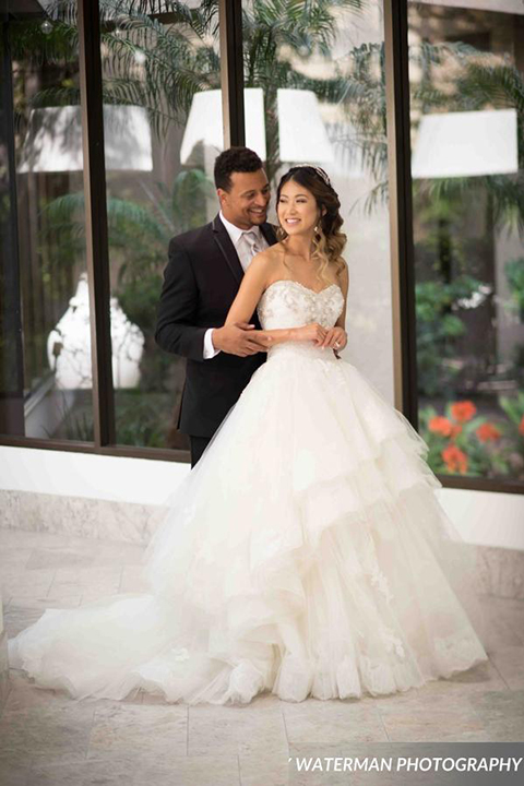 Classic glamour wedding shoot at the avenue of the arts hotel bride strapless ball gown with beaded detail on top with sweetheart neckline and groom black tuxedo with white dress shirt and long silver tie with matching vest and pocket square hugging