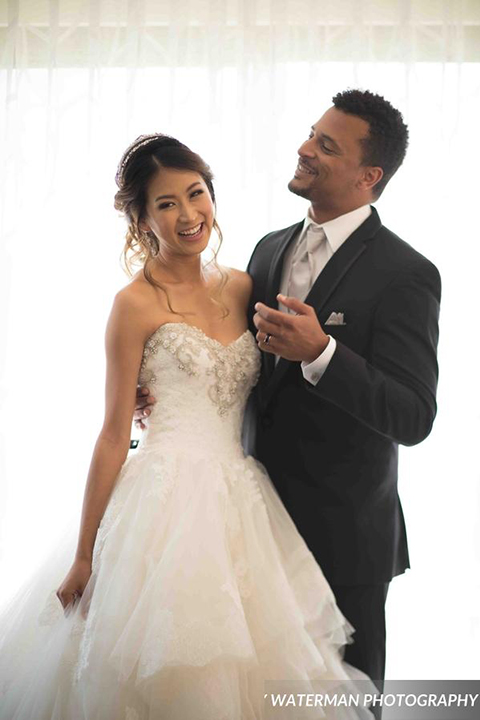 Classic glamour wedding shoot at the avenue of the arts hotel bride strapless ball gown with beaded detail on top with sweetheart neckline and groom black tuxedo with white dress shirt and long silver tie with matching vest and pocket square hugging and smiling