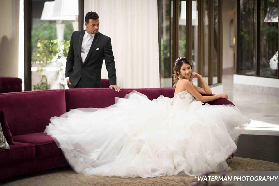 Classic glamour wedding shoot at the avenue of the arts hotel bride strapless ball gown with beaded detail on top with sweetheart neckline and groom black tuxedo with white dress shirt and long silver tie with matching vest and pocket square bride sitting on couch