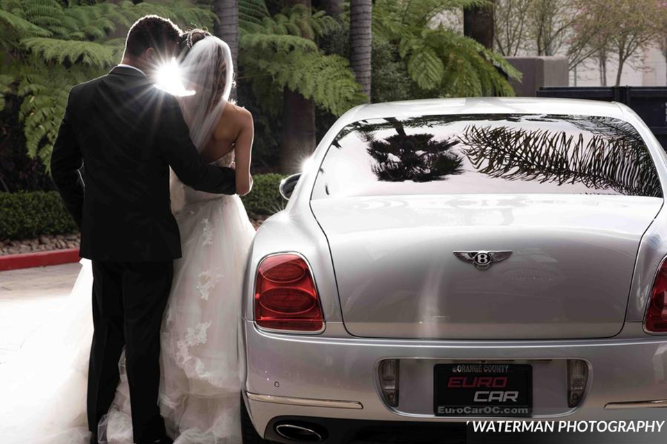 Classic glamour wedding shoot at the avenue of the arts hotel bride strapless ball gown with beaded detail on top with sweetheart neckline and groom black tuxedo with white dress shirt and long silver tie with matching vest and pocket square hugging by car