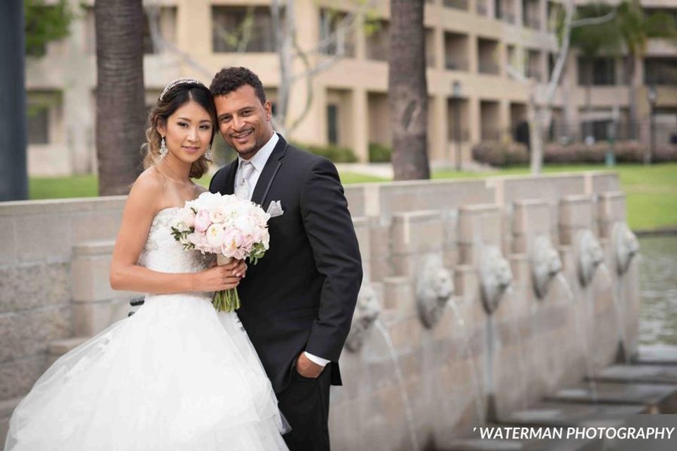 Classic glamour wedding shoot at the avenue of the arts hotel bride strapless ball gown with beaded detail on top with sweetheart neckline and groom black tuxedo with white dress shirt and long silver tie with matching vest and pocket square