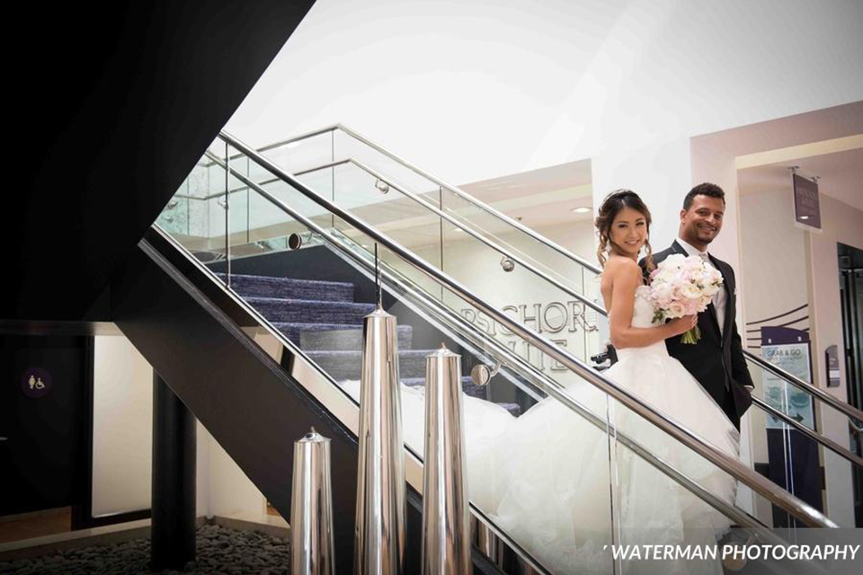 Classic glamour wedding shoot at the avenue of the arts hotel bride strapless ball gown with beaded detail on top with sweetheart neckline and groom black tuxedo with white dress shirt and long silver tie with matching vest and pocket square walking down stairs