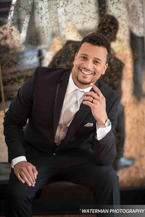 Classic glamour wedding shoot at the avenue of the arts hotel groom black tuxedo with white dress shirt and long silver tie with matching vest and pocket square smiling