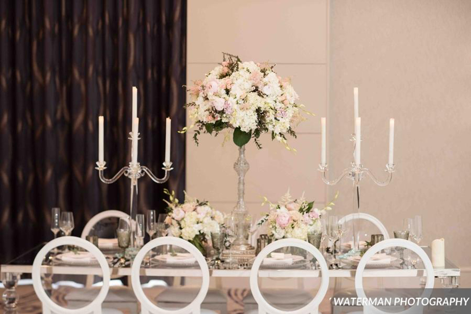 Classic glamour wedding shoot at the avenue of the arts hotel table set up with glass mirror table and white place settings with white and pink flower centerpiece decor with tall white candles and white chairs wedding photo idea for tables