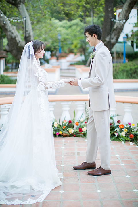 Rancho las lomas spanish inspired wedding shoot bride form fitting strapless lace gown with sweetheart neckline and long veil with lace trim and crystal belt with groom tan suit with matching vest and white dress shirt with dark grey bow tie holding hands