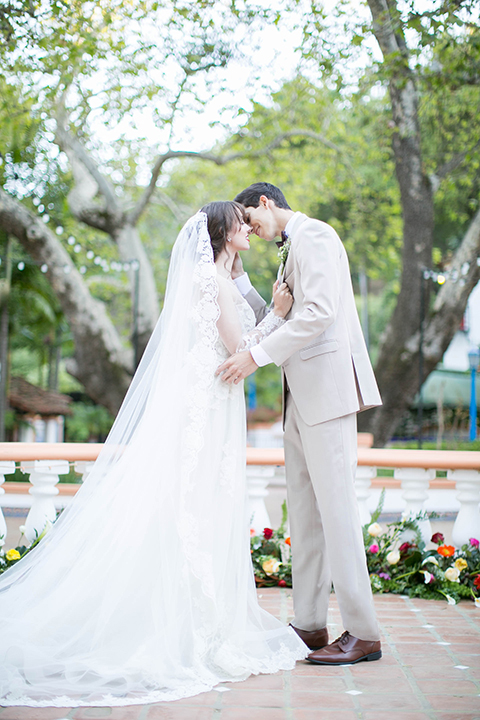 Rancho las lomas spanish inspired wedding shoot bride form fitting strapless lace gown with sweetheart neckline and long veil with lace trim and crystal belt with groom tan suit with matching vest and white dress shirt with dark grey bow tie kissing