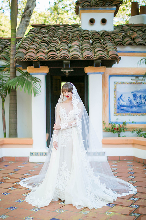 Rancho las lomas spanish inspired wedding shoot bride form fitting strapless lace gown with sweetheart neckline and long veil with lace trim and crystal belt