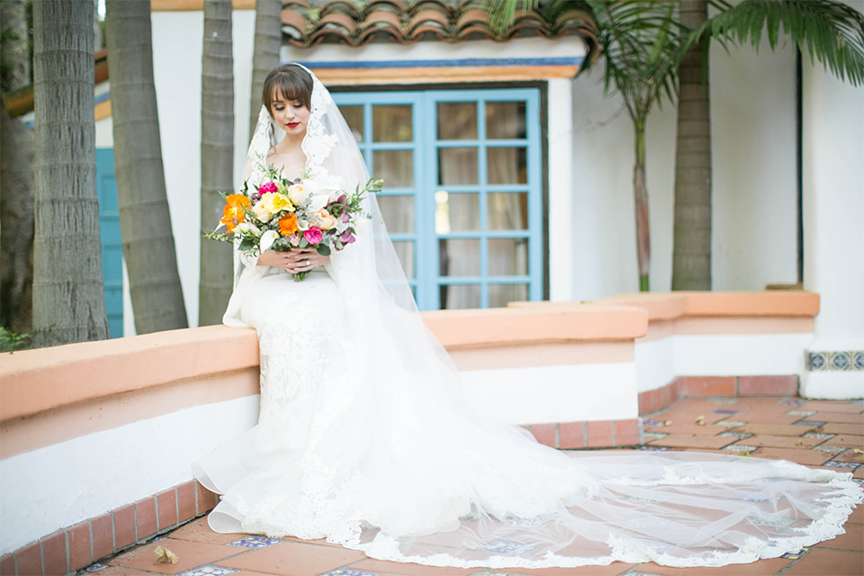 Rancho las lomas spanish inspired wedding shoot bride form fitting strapless lace gown with sweetheart neckline and long veil with lace trim and crystal belt holding floral bridal bouquet